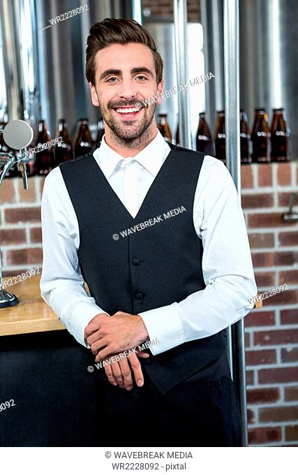 Handsome barman leaning on counter