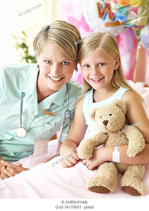 Girl with teddy bear and nurse in hospital