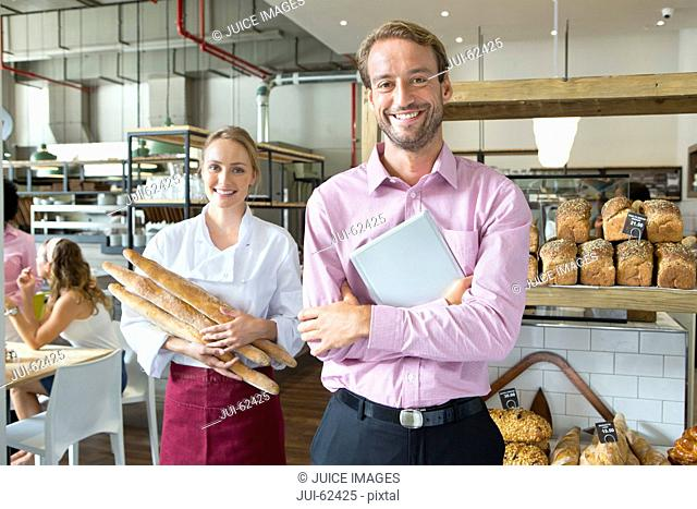 Smiling baker with business owner holding bread in bakery