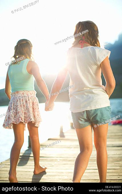 Sisters holding hands on dock over lake