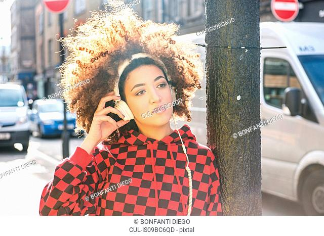 Portrait of young woman outdoors, wearing headphones, pensive expression