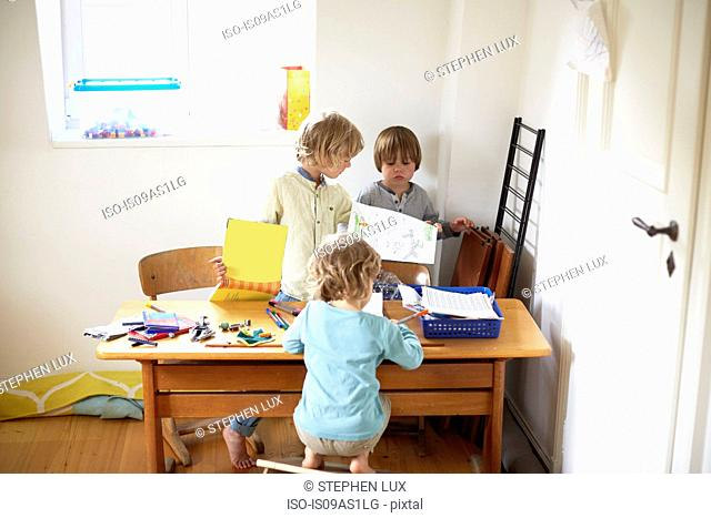 Three boys sitting at table drawing pictures