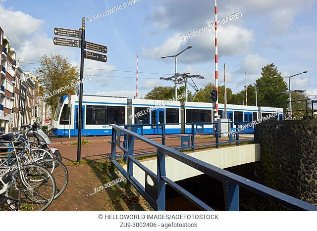 Tram crossing Hortusbrug a bascule bridge across Nieuwe Herengracht canal, Amsterdam, Netherlands