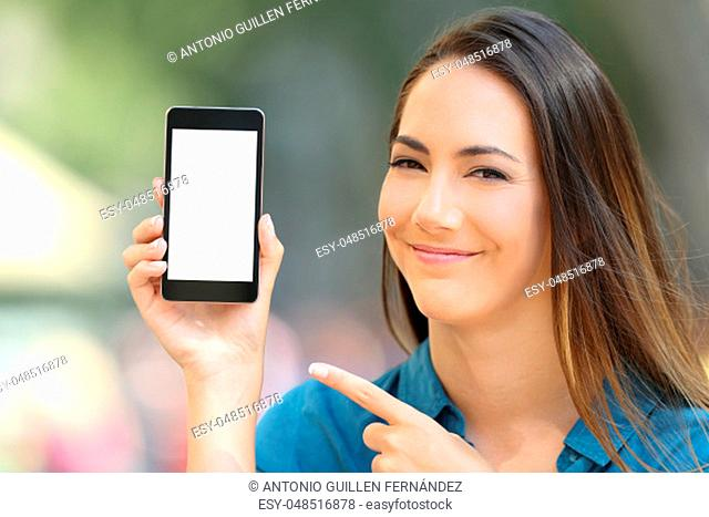 Satisfied woman pointing at a blank phone screen mock up on the street