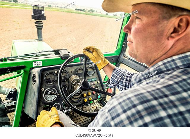Close up of male farmer driving tractor in ploughed field