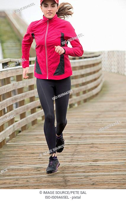 Woman running on wooden dock