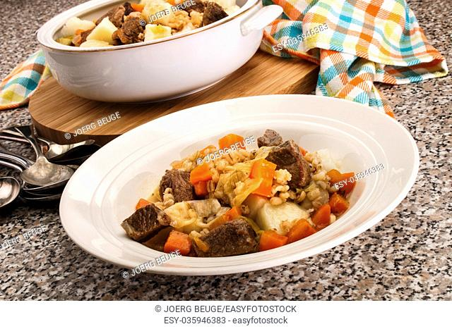 served irish beef and barley stew in a deep white plate