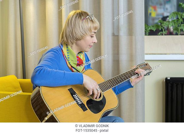 Smiling woman playing acoustic guitar at home