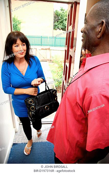 Elderly black man greeting white woman carer at front door