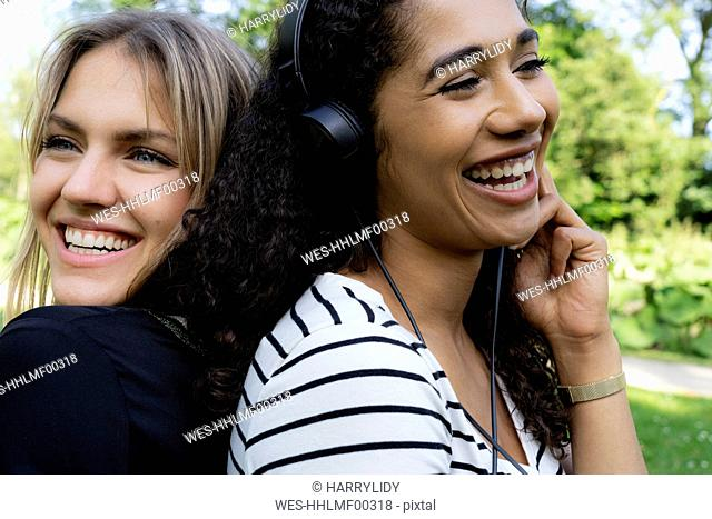 Two girlfriends in a park listening music, laughing, having fun