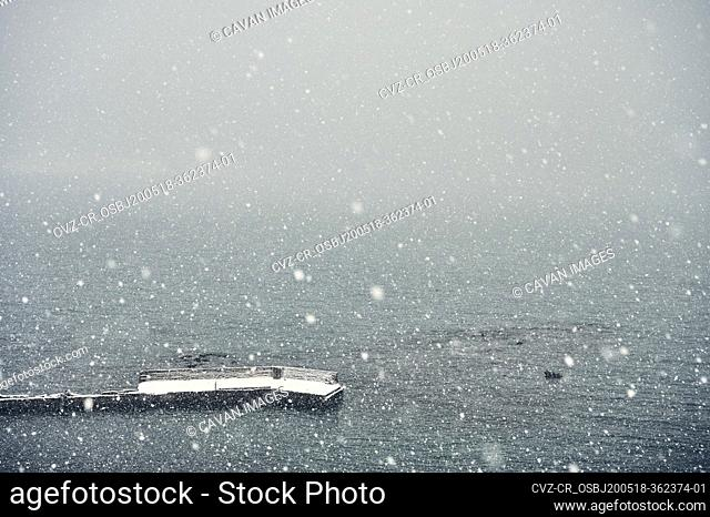 Spectacular seascape with pier during snowfall