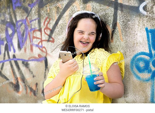 Teenager with down syndrome using smartphone, holding plastic cup