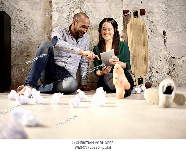 Smiling colleagues sitting on office floor sharing tablet