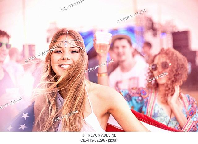 Portrait smiling young woman with American flag at music festival