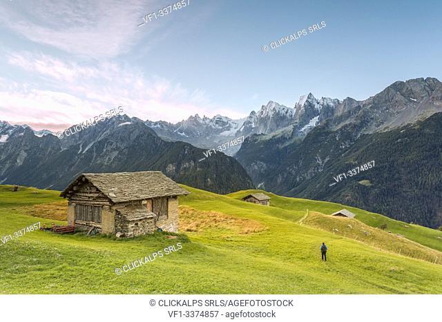 Hiker admiring from an alpine hut the snowy peaks in the background, Tombal, Soglio, Bregaglia Valley, canton of Graubünden, Switzerland, Europe