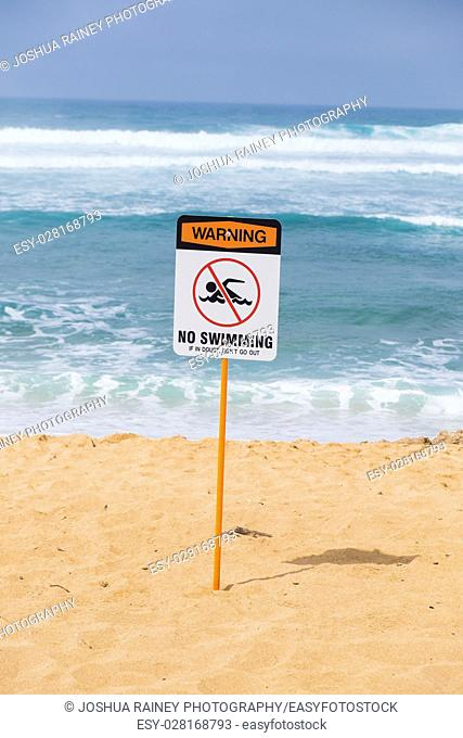 Storng current no swimming sign in front of a popular surf spot at Haleiwa Beach on Oahu Hawaii