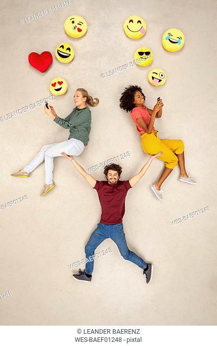 Man balancing two women, chatting on their smart phones