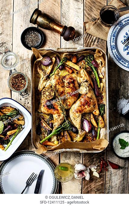 Whole butterflied roasted chicken with vegetables on wooden table