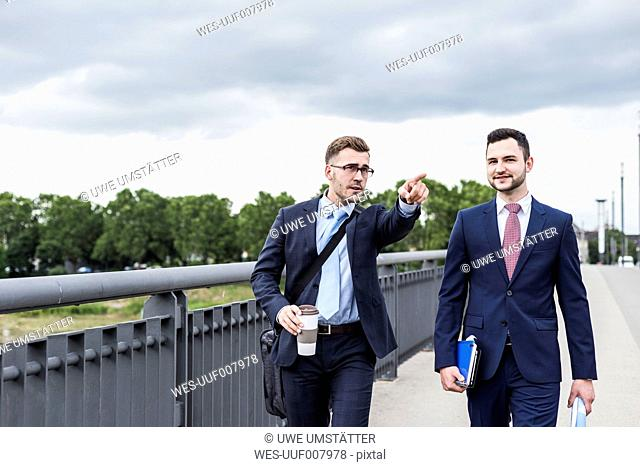 Two young businessmen walking together in the city