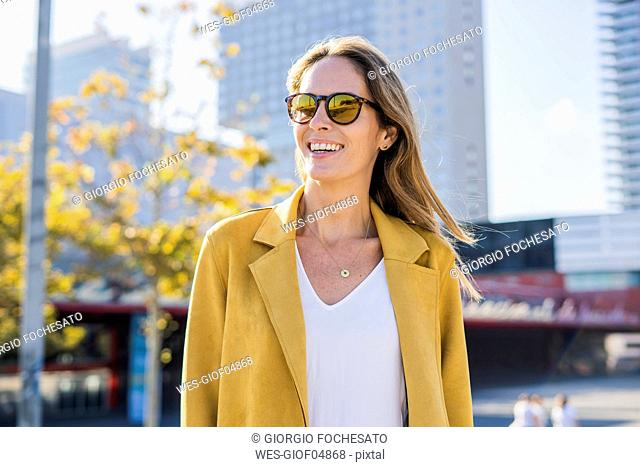 Portrait of smiling woman wearing sunglasses in the city