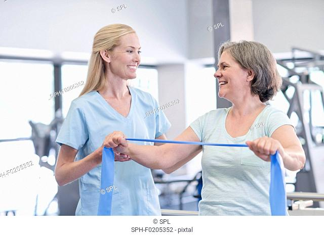 Nurse showing woman how to use resistance band