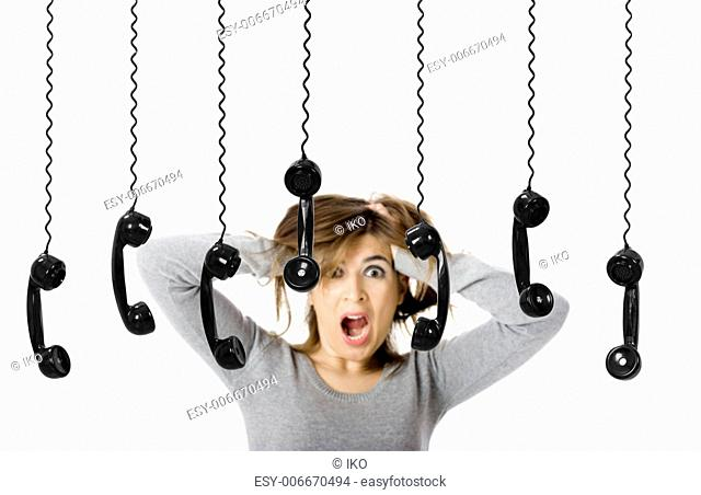 Beautiful woman in shock looking to a lot of telephones