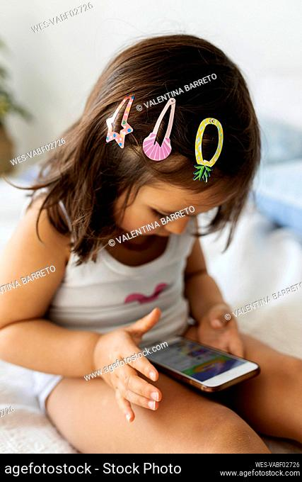 Little girl with three hair clips sitting on bed looking at smartphone