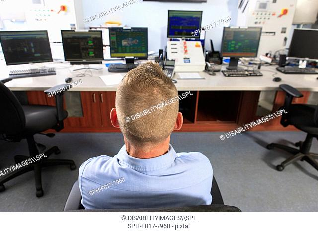 Engineer at electric power plant control room watching management displays