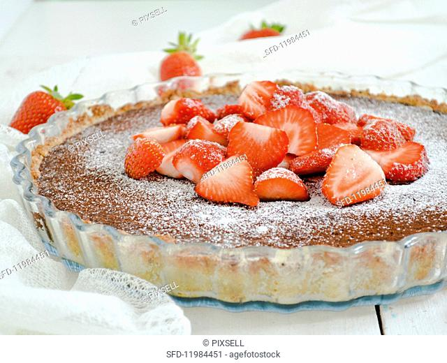 A chocolate tart topped with strawberries and icing sugar