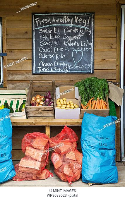 Handwritten blackboard on wall and crates with fresh vegetables and stack of firewood in red net bags outside a farm shop