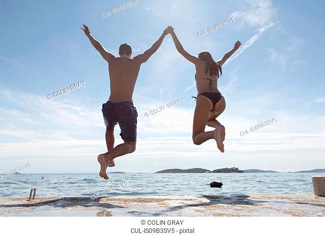 Young couple jumping into sea, rear view, Orebic, Croatia