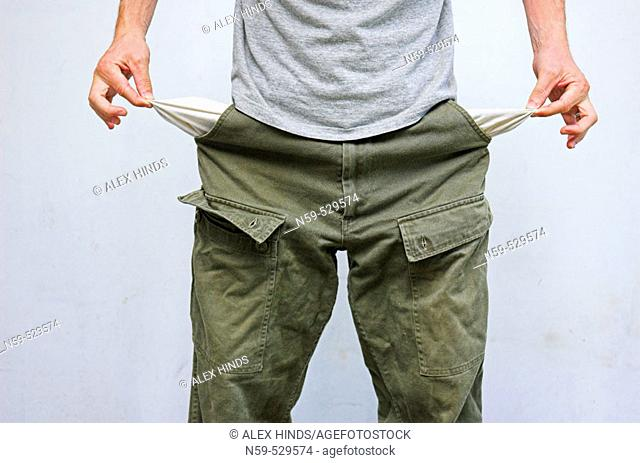 Young man pulling his pockets out to illustrate lack of money
