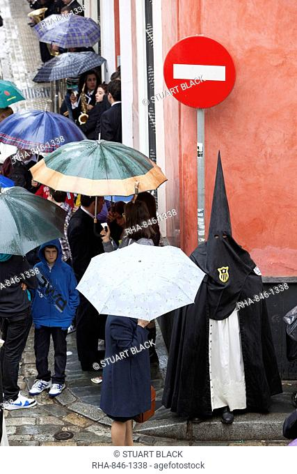 Penitent during Semana Santa (Holy Week) along rainy street, Seville, Andalucia, Spain, Europe