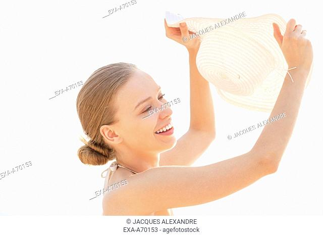 woman with white sun hat protecting her face against sun