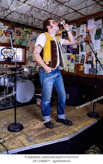 Beatnick looking male chugging beer onstage decorated with posters and a drum set wearing cuffed jeans