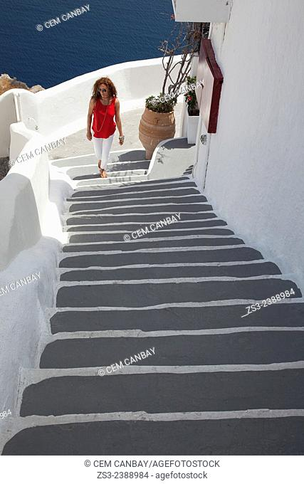Woman walking up the stairs in town center, Oia, Santorini, Cyclades Islands, Greek Islands, Greece, Europe
