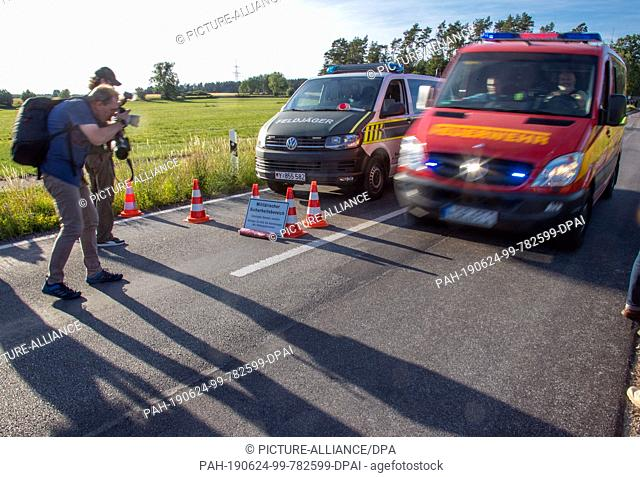 24 June 2019, Mecklenburg-Western Pomerania, Nossentiner Hütte: A fire engine passes the roadblock of the Bundeswehr military police on the access road to the...