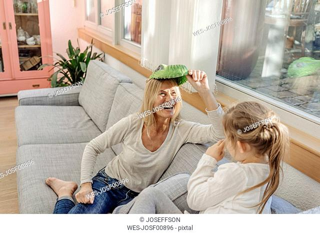 Playful mature woman and girl at home on couch
