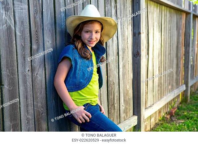 Children girl as kid cowgirl posing on wooden fence