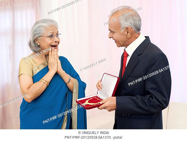 Man giving jewelry to his wife on their anniversary