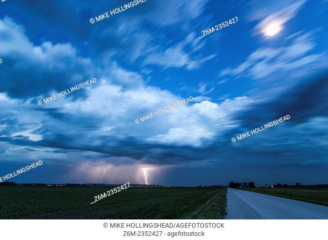 Lightning hits the ground in southwest Iowa as the moon shines brightly under twilight conditions