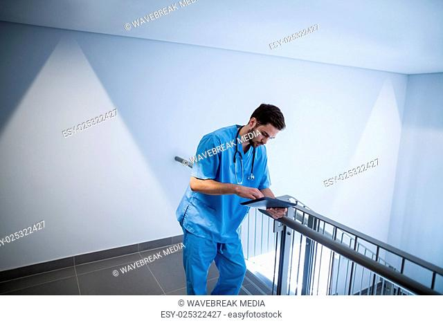 Male nurse using digital tablet in corridor