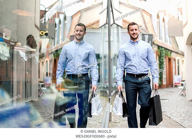 Smiling young man with shopping bags outside a shop