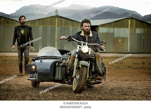 Two men with full beards with motorcycle with sidecar