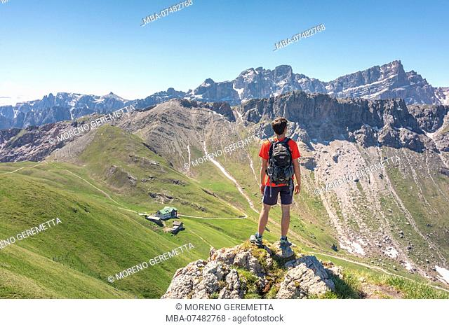 Hiker on the Zendleser Kofel / Col di Poma looking to the valley with Genova hut and Gampen alm , Mount Medalges and the Puez Odle / Geisler Group, Funes Valley