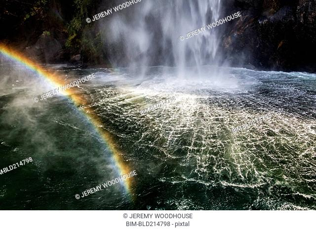 High angle view of rainbow over waterfall flowing into river