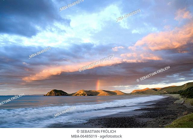 Dramatic sundown with rainbow and cloud formation with port Jackson in New Zealand. Lonesome beach in the foreground