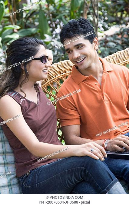 Young couple sitting on a couch and smiling