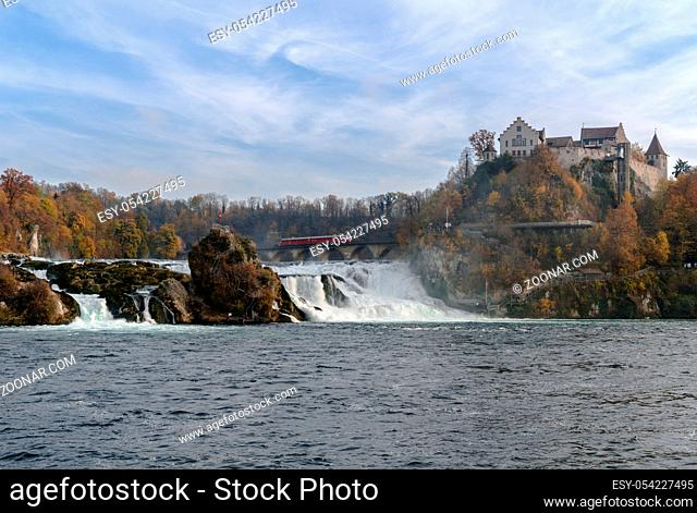 horizontal view of a a red arrow train stopping on top of the bridge at Rhine Falls to view the wonderful waterfall landscape and the castle at Laufen in...