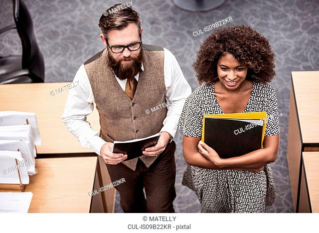 Businesswoman and man carrying files in office